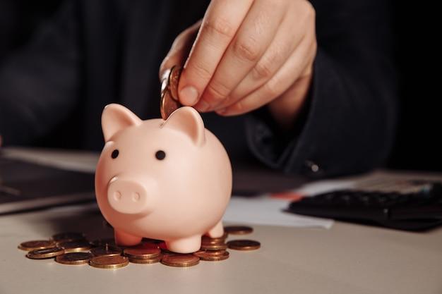 Pièces éparses et tirelire rose au bureau. concept financier et commercial
