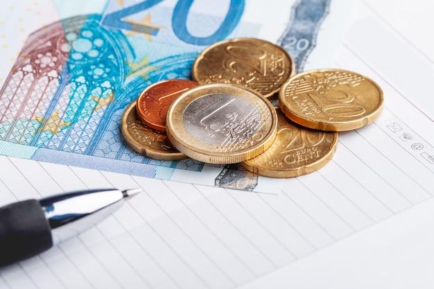 Pièces en euros et billets de banque avec une feuille de papier et un stylo