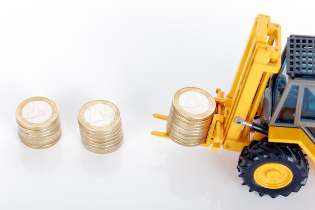 Pièces en euros et chariot élévateur sur espace blanc