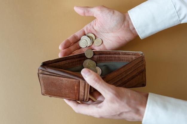 Pièces en main et dans un portefeuille vide