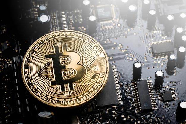 Les pièces de médaille d'or en monnaie crypto sur carte graphique et chipset de la carte mère noire.