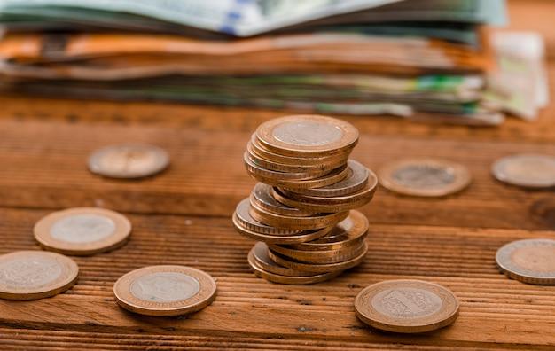 Pièces de monnaie, billets de banque sur table en bois.