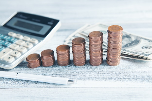 Pièces de monnaie, billets et une calculatrice sur la table