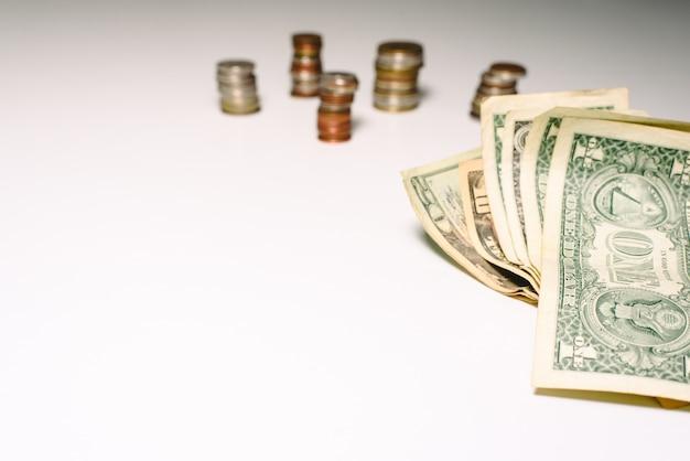 Pièces de monnaie et billets d'un dollar isolés sur fond blanc avec espace de copie.