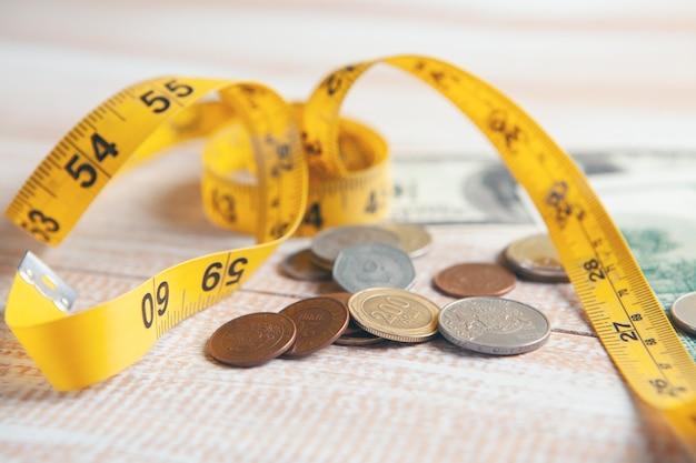Pièces de monnaie, billets d'un dollar et ruban à mesurer sur la table