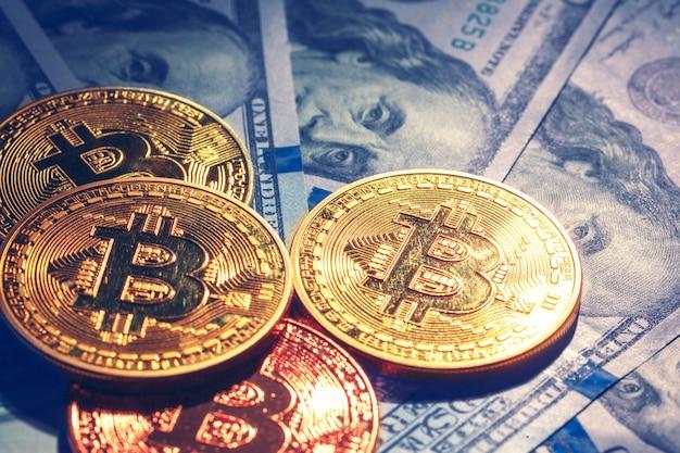 Pièces de monnaie bitcoin d'or sur une monnaie de papier dollars