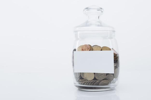 Pièces de monnaie dans une banque de verre avec espace pour le texte
