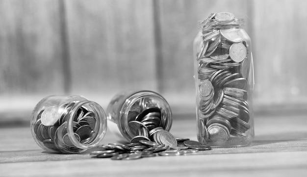 Pièces de monnaie dans un bocal sur le sol. pièces accumulées sur le sol. économies de poche en tas.