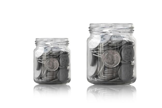 Pièces de monnaie dans un bocal en verre contre, pièces d'épargne - concept d'investissement et d'intérêt économisant de l'argent, de plus en plus d'argent sur la tirelire. isolé sur fond blanc