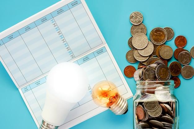 Pièces de monnaie dans un bocal en verre et à l'extérieur avec ampoule rougeoyante, lampe à led et livre de correspondance sur le bleu
