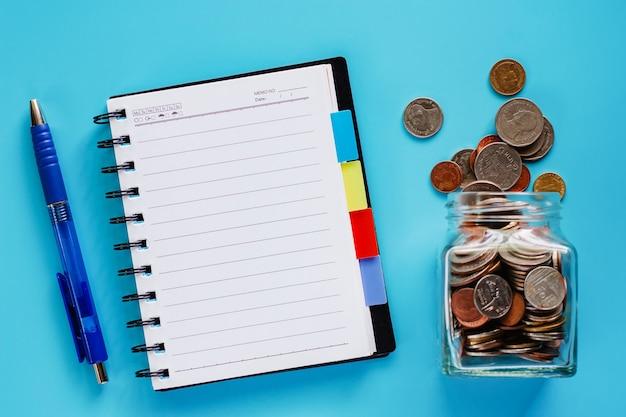 Pièces de monnaie dans un bocal en verre et à l'extérieur, argent en monnaie thaïlandaise avec cahier à spirale vierge et stylo