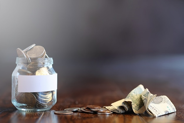 Pièces de monnaie dans un bocal en verre sur un plancher en bois. économies de poche des pièces de monnaie à la banque. tirelire dans un bocal en verre avec des pièces de monnaie.