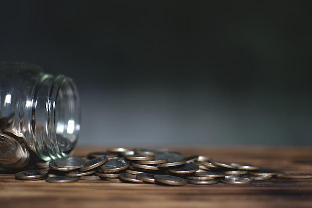 Pièces de monnaie dans le bocal en verre sur une vieille planche de bois