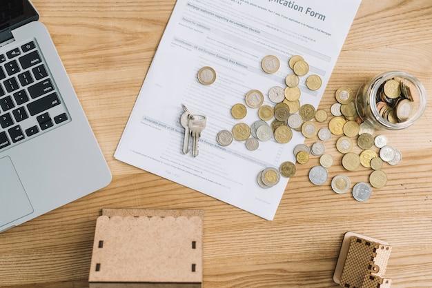 Pièces de monnaie et demande de prêt hypothécaire près d'un ordinateur portable
