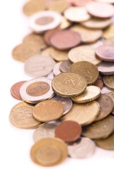 Pièces de monnaie de différents pays sur fond blanc.