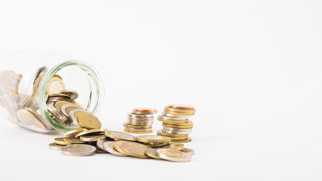 Pièces de monnaie éparpillées dans un bocal en verre