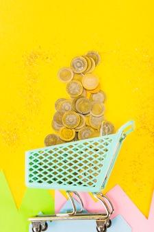 Pièces de monnaie éparpillées dans un petit panier d'épicerie