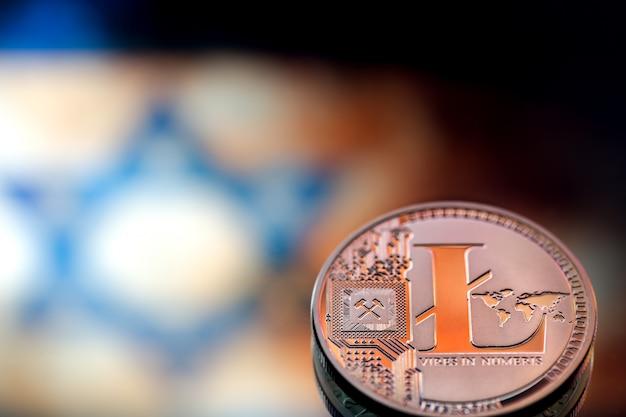 Pièces de monnaie litecoin, contre le drapeau israélien, concept d'argent virtuel, gros plan. image conceptuelle