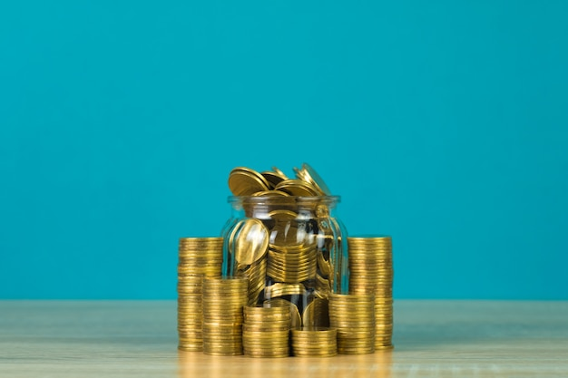 Pièces de monnaie et monnaie d'or dans le bocal en verre