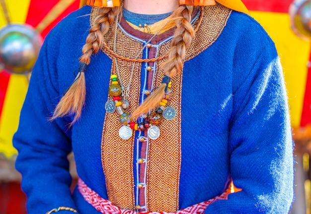 Pièces de monnaie et ornements antiques sur les vêtements de la femme médiévale.