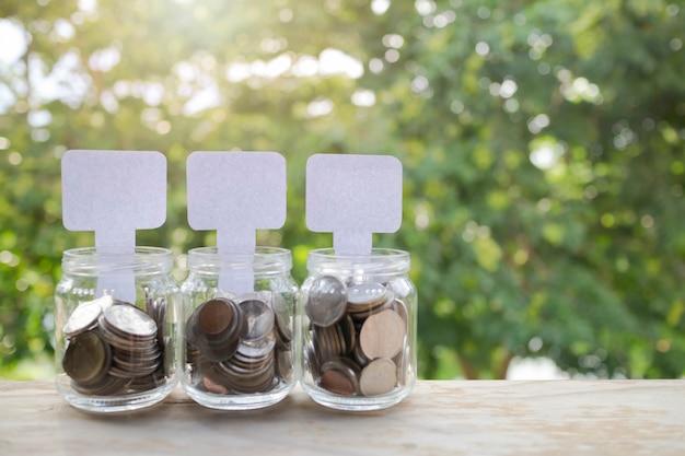 Pièces de monnaie et papier blanc dans le verre, finance d'entreprise et épargne en grandissant concept.