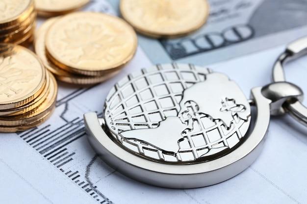 Pièces de monnaie, papier-monnaie et globe sur fond blanc