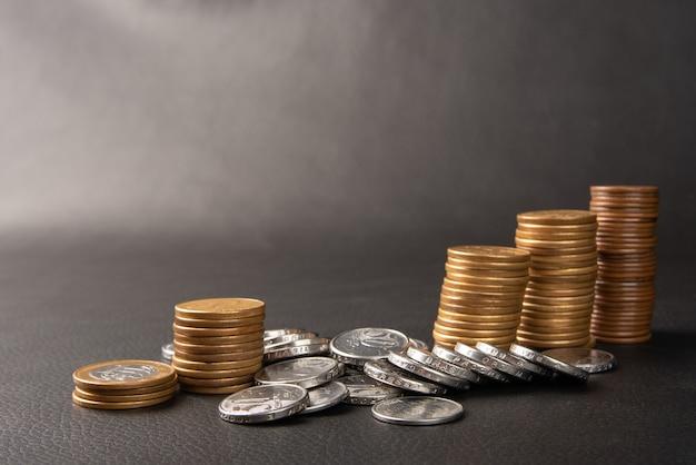 Pièces de monnaie, pièces de monnaie brésiliennes de différentes valeurs â€empilées sur cuir noir, mise au point sélective.