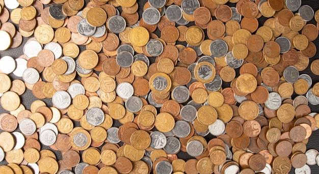 Pièces de monnaie, pièces de monnaie brésiliennes de différentes valeurs â€étalées sur une surface en cuir noir, vue de dessus.