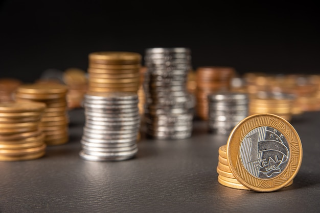 Pièces de monnaie, pièces de monnaie brésiliennes de divers montants empilées et une vraie pièce de monnaie au premier plan sur cuir noir, mise au point sélective.