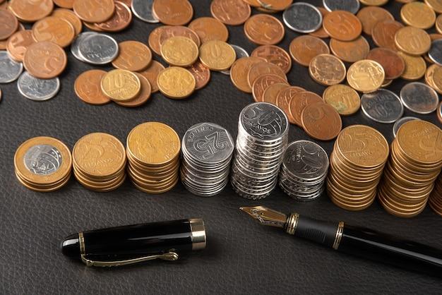 Pièces de monnaie, pièces de monnaie brésiliennes de divers montants entassés et un stylo plume sur cuir noir, mise au point sélective.