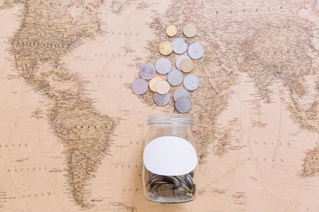 Pièces de monnaie et un pot ouvert sur la carte du monde