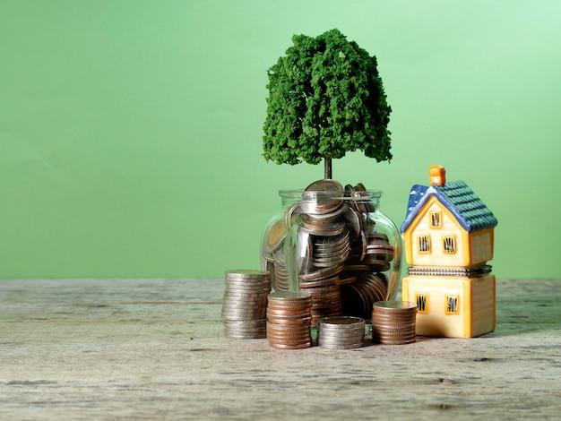 Pièces de monnaie en pot de verre avec modèle de maison sur une table en bois