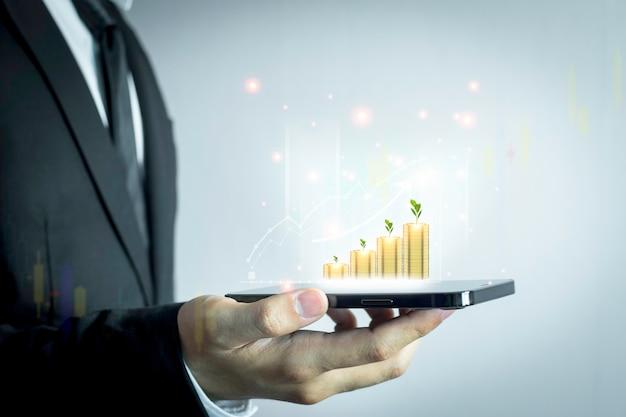Les pièces de monnaie pour faire croître vos entreprises utilisent une technologie innovante de graphique boursier. technique mixte, smartphone numérique et concept en ligne.