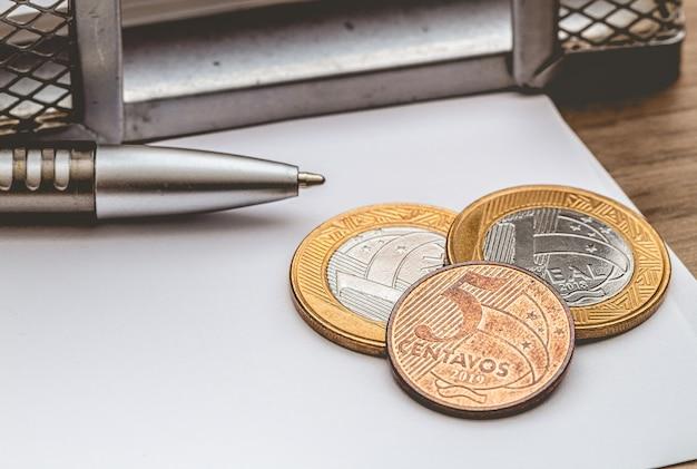 Pièces de monnaie réelles brésiliennes sur du papier blanc en gros plan