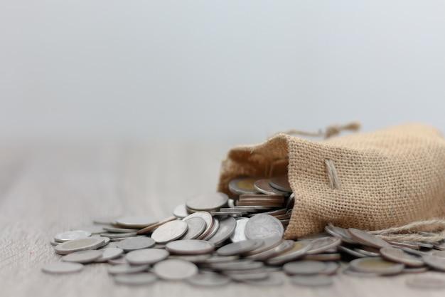 Pièces de monnaie en sac sur la table en bois