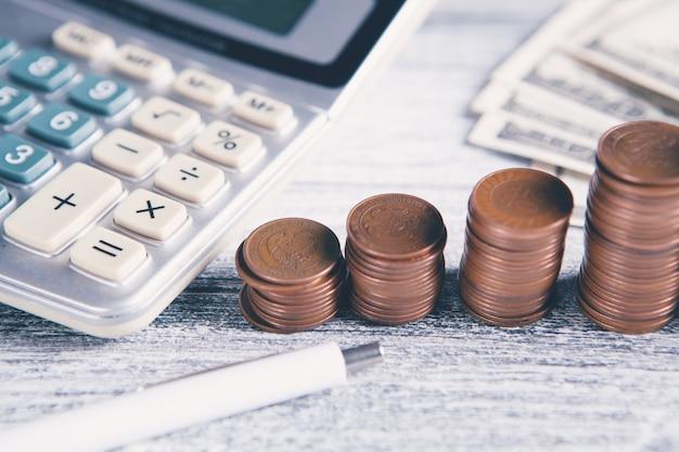 Pièces de monnaie, stylo, billets et calculatrice
