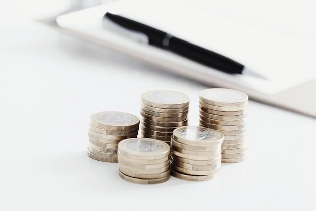 Pièces de monnaie et stylo sur table en bois