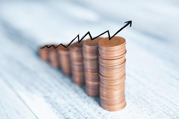Pièces de monnaie sur la table sous la forme d'un graphique croissant et d'une flèche vers le haut