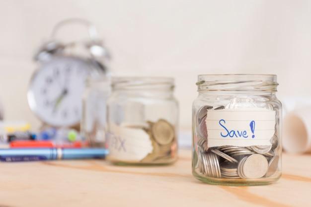 Pièces de monnaie en verre avec économiser du papier et des pièces à l'intérieur et fond de l'horloge floue