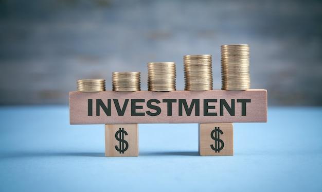 Pièces avec mot d'investissement et symbole du dollar.
