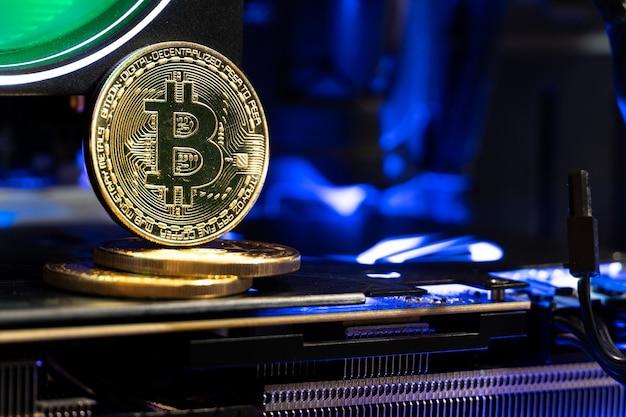 Pièces d'or bitcoin sur une carte mère avec néon.