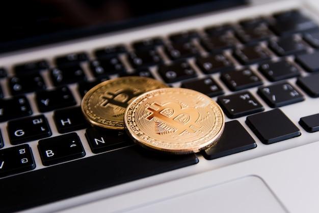 Pièces d'or bitcoin sur clavier ordinateur portable avec fond de graphique à échanger