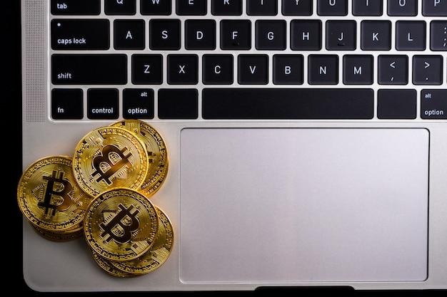 Pièces d'or avec symbole bitcoin sur ordinateur.