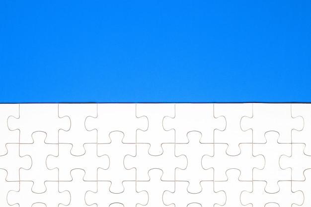 Pièces de puzzle blanc sur fond bleu. contexte du contenu
