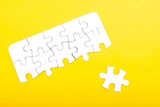 Pièces de puzzle blanc isolés sur fond jaune