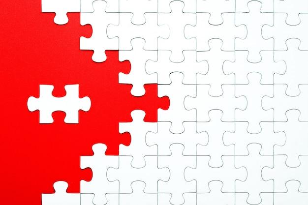 Pièces de puzzle blanches sur fond rouge séparées