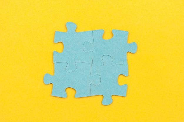 Pièces de puzzle bleu sur un concept d'entreprise de fond jaune