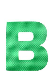 Pièces de puzzle colorées en mousse alphabet sur fond blanc.