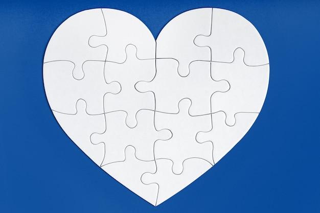 Pièces de puzzle en forme de coeur sur bleu