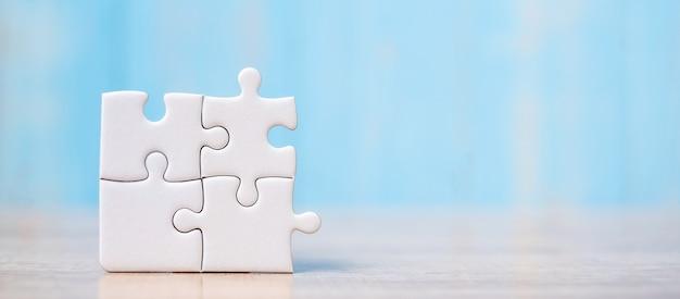 Pièces de puzzle sur table en bois. solutions, objectif de la mission